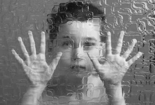 Niño mirando a través de un cristal