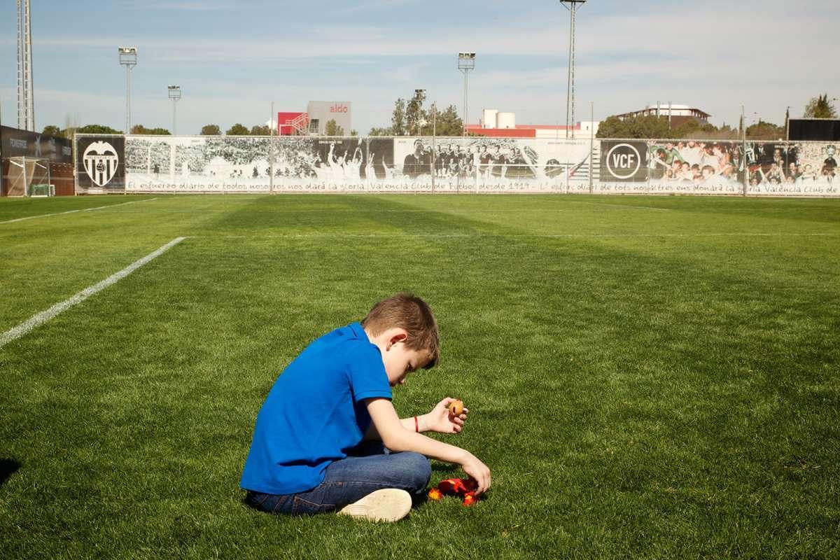 Niño sentado sobre campo de fútbol